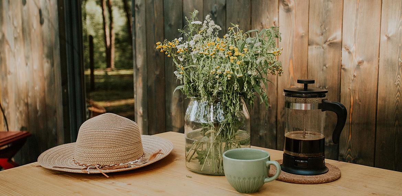 Widok na stół na tarasie z kwiatami i pyszną kawą