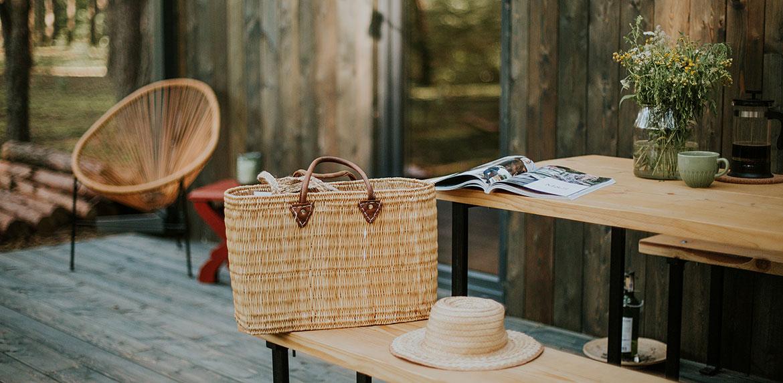 Widok na stół na tarasie na nim torba i kapelusz w tle magazyn i fotel