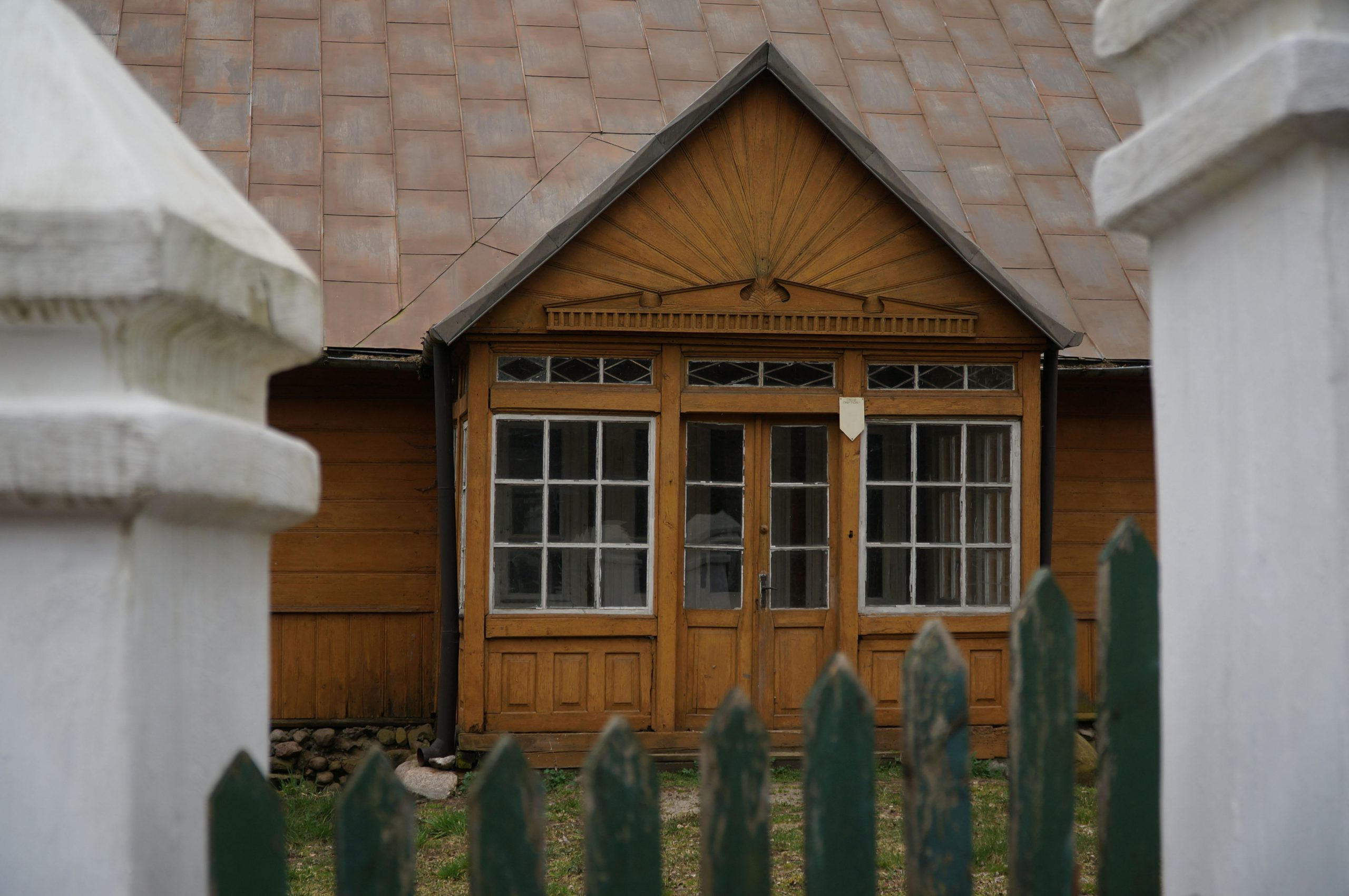 wisok na stary dom przez bramę wjazdową